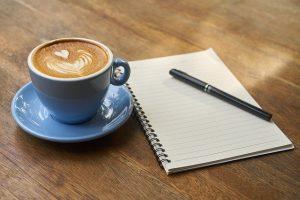 Tasse Kaffee und Notizblock mit Stift auf Tisch