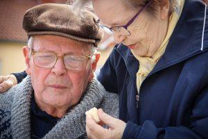 Alte Frau hilft Mann mit Essen