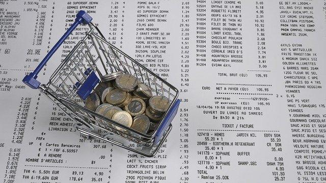 Kleiner Einkaufswagen mit Euromünzen auf Bons