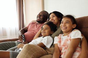 Familie sitzt auf Sofa und schaut fern