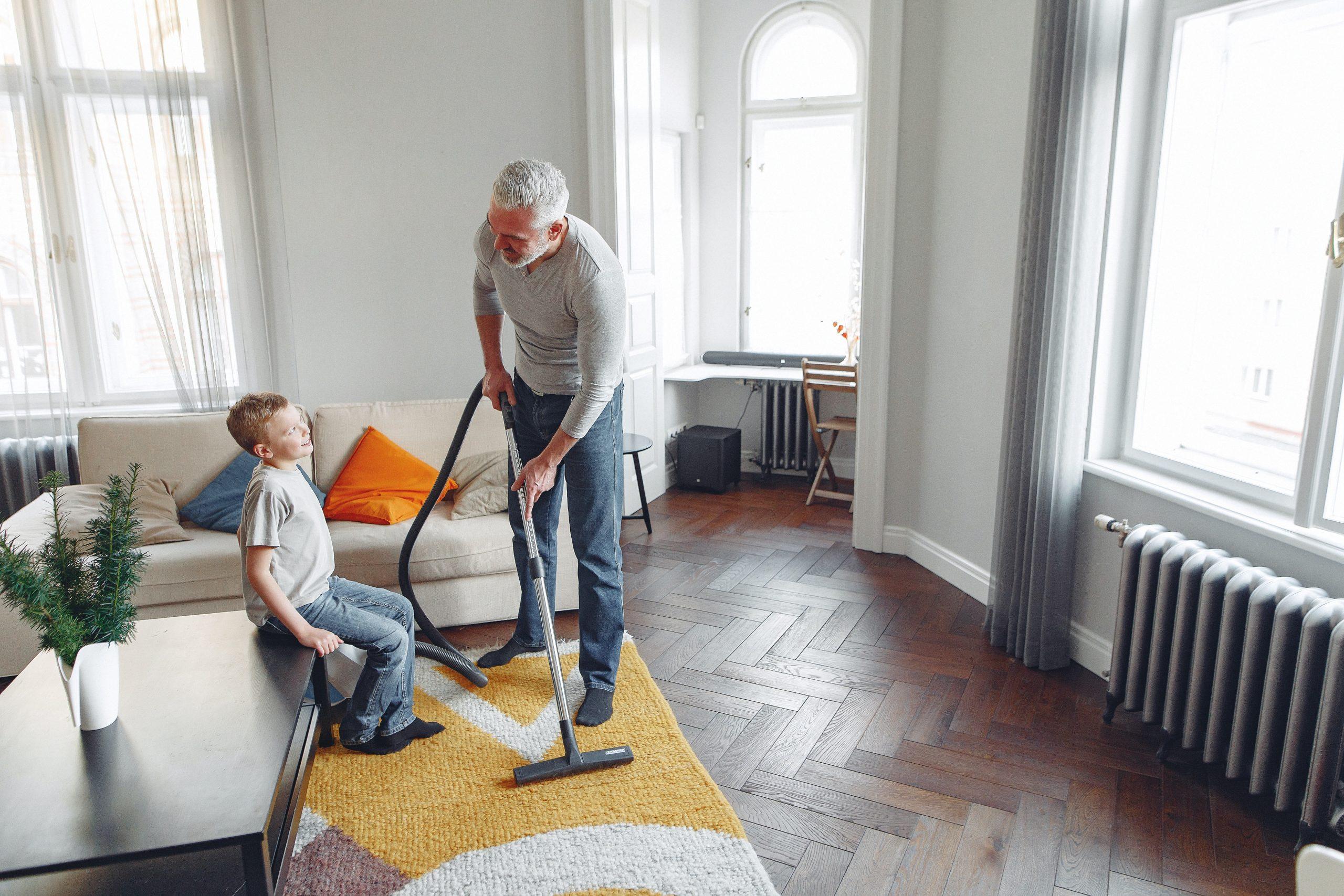 Vater und Sohn saugen Wohnzimmer
