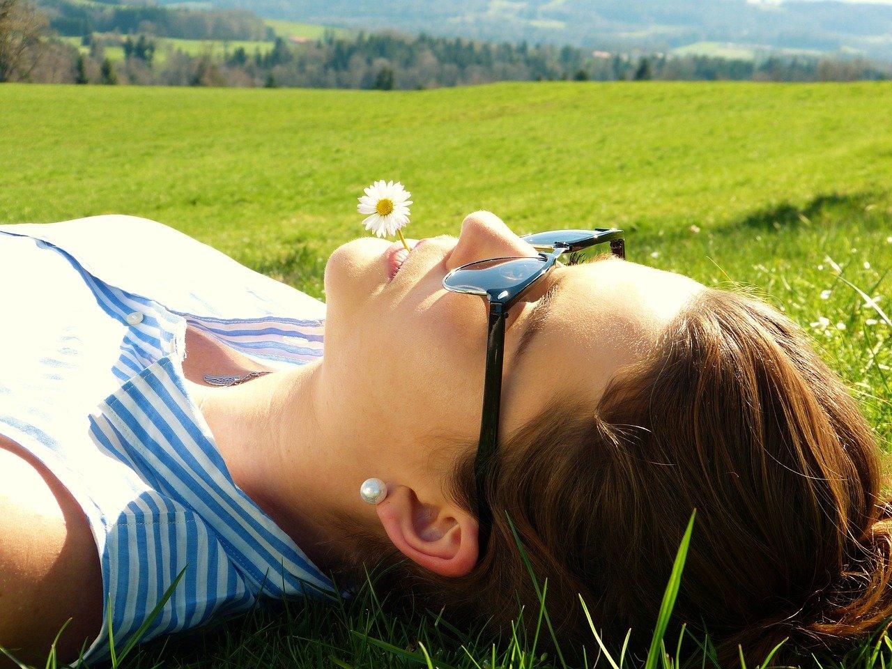 Frau liegt auf Wiese und entspannt