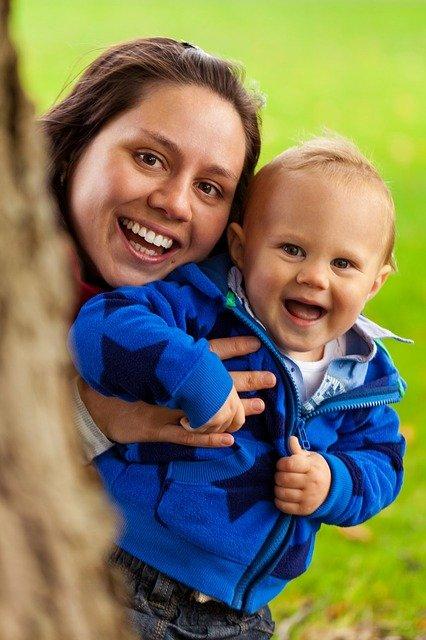 Frau und Kind neben Baum lachen in Kamera