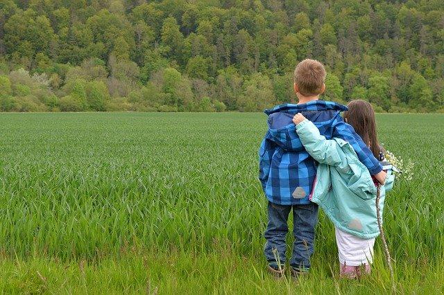 Zwei Kinder schauen sich umarmend auf Feld
