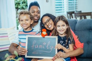 Familie mit Pflegekindern auf Sofa