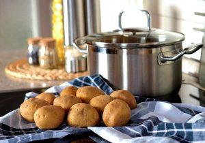 Topf, Tuch und Kartoffeln auf Herd